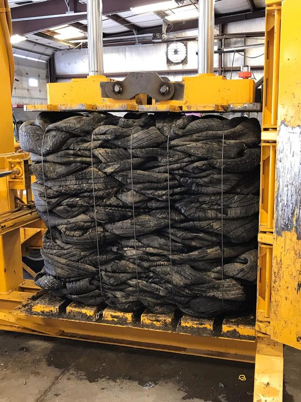 Scrap tires being baled into a block.