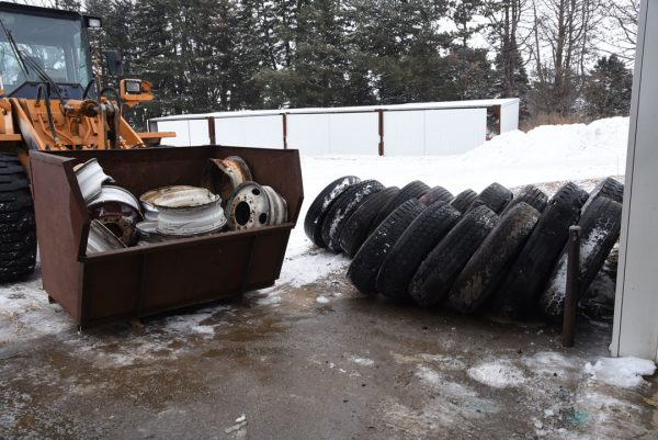 A stack of scrap tires with the rims removed and a bin full of scrap rims.
