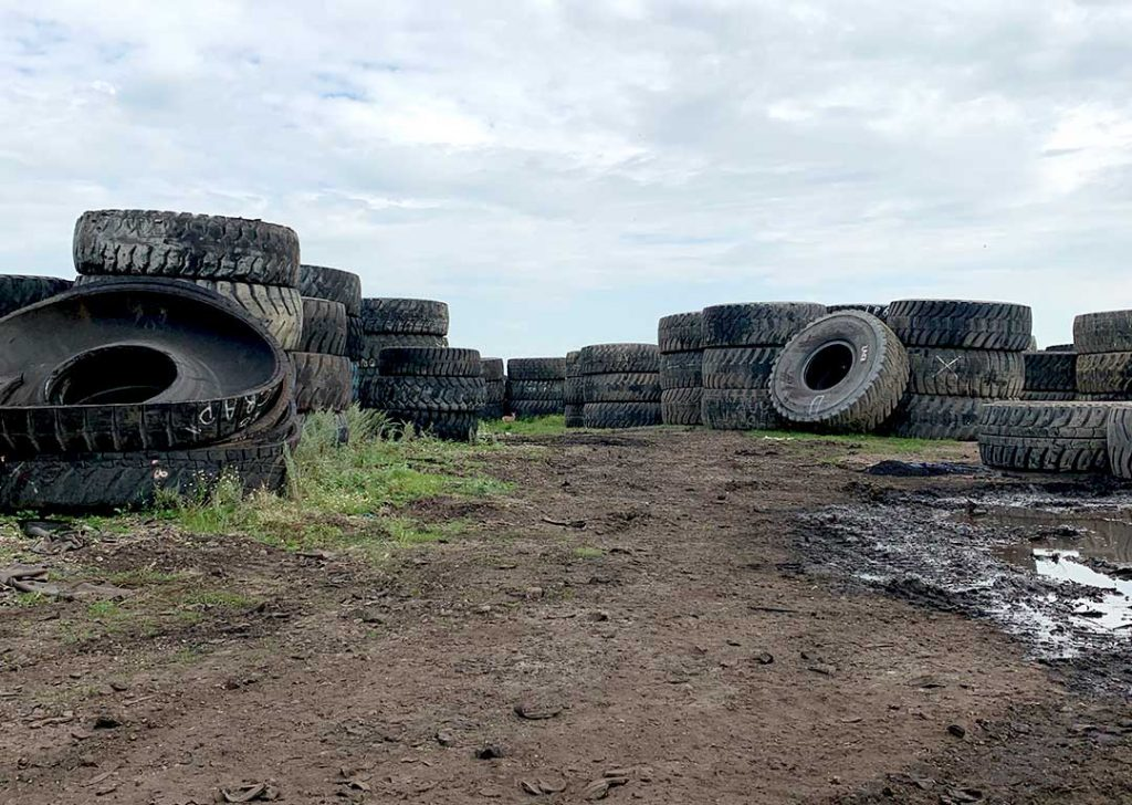 Piles of OTR mining tires waiting to be recycled