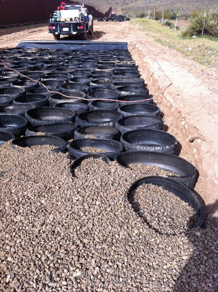 Tire treads filled with aggregate to create road bases.
